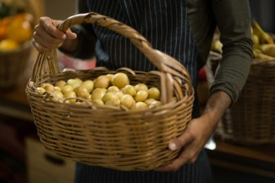 Vendor holding basket of potatoes at the grocery store - vendor holding basket of potatoes at the grocery store 400x267
